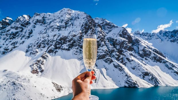 shu-gen-Person-holding-champagne-background-mountain-1281816907-1440x823